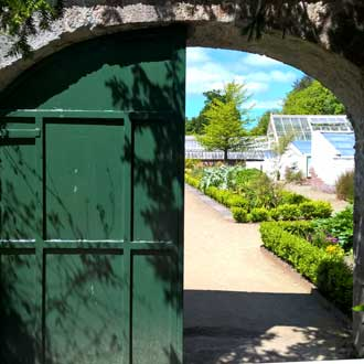 View into the frameyard through a half open gate. Glass houses and hedges can be seen in the background