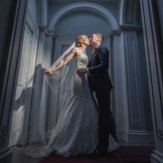 Wedding couple kissing bathed in the light from an upper window
